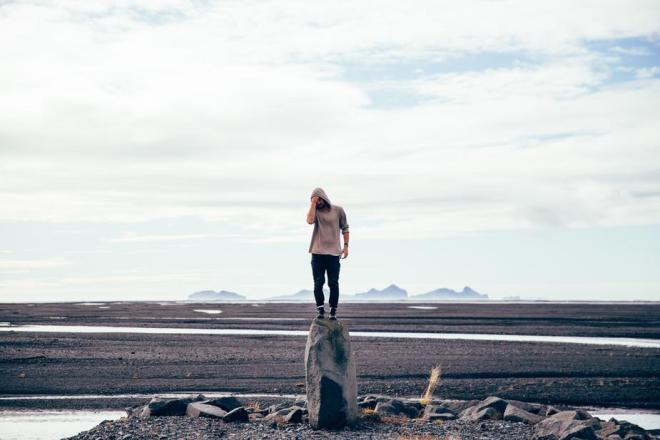 man-standing-on-tall-rock_925x